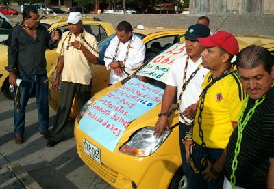 Taxistas encadenados a sus vehículos en la Plaza de la Paz de Barranquilla.